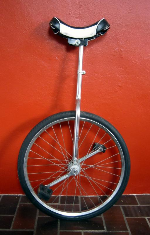 A clown often performs a routine on a unicycle.